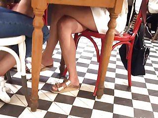Sexy crossed legs feets miniskirt under table