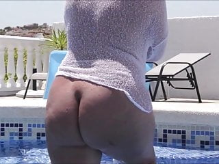 A mature woman tempts with her ass by walking by the pool